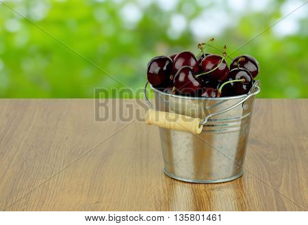 Ripe juicy sweet cherries in a small metal bucket on a wooden background with a blurred natural background. Season goodies. Snack. Diet. Natural vitamins.