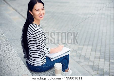 Share your emotions. Cheerful delighted beautiful young woman sitting on the footsteps and smiling while making notes
