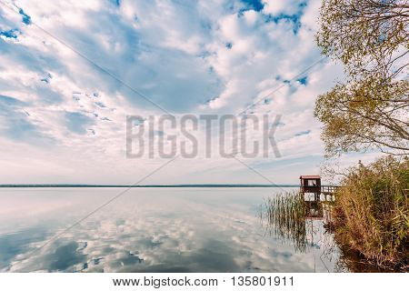 Old Wooden Pier For Fishing, Small House Or Shed And Beautiful Lake Or River In Background.