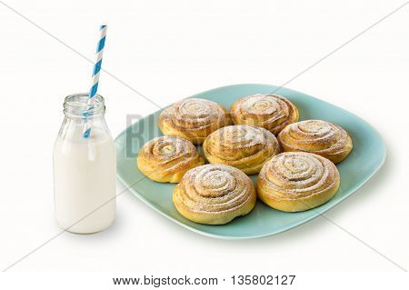 Kanelbulle - swedish cinnamon rolls on a blue plate and milk bottle