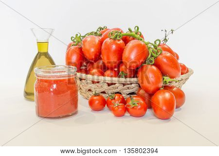 Bunch of red tomatoes in a basket with olive oil and tomato juice
