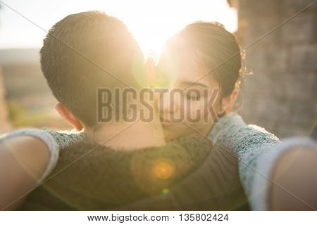 Young couple in love hugging in the nature enjoying and looking in the sunset Close up portrait of attractive young couple outdoors.Pretty couple celebrating anniversary. First kiss. Love. Happiness.
