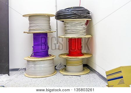 Stacked various cable spools are waiting to be used in new edifice.