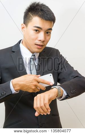 Young Asian Business Man Looking At Watch And Talking On Cellphone