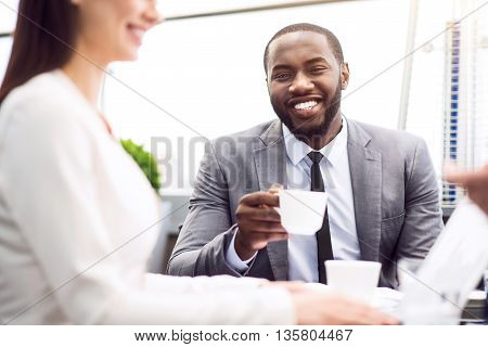 Rise your mood. Cheerful delighted smiling man sitting at the table and drinking coffee while working in the office with his colleague