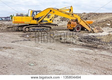 View on excavator with caterpillar who is parked at construction site.
