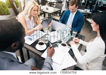 Like your work. Pleasant cheerful colleagues sitting at the table and working together while expressing gladness