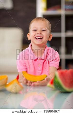Happy cute little boy eating watermelon at home
