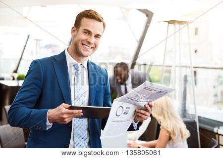 Look positively. Cheerful delighted smiling man holding newspaper and using tablet while his colleagues sitting in the background