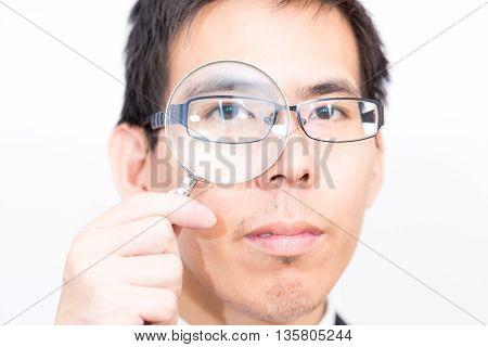 Business Asian Man Looking At Camera Through Magnifying Glass