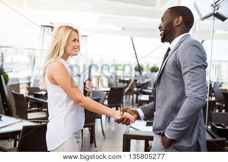 Nice to work with you. Positive cheerful professional colleagues looking at each other and shaking hands while expressing gladness