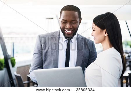 Have a look. Cheerful smiling colleagues standing together and discussing project while using laptop