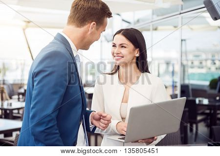 Positive attitude. Cheerful smiling colleagues standing in the office and talking while using laptop