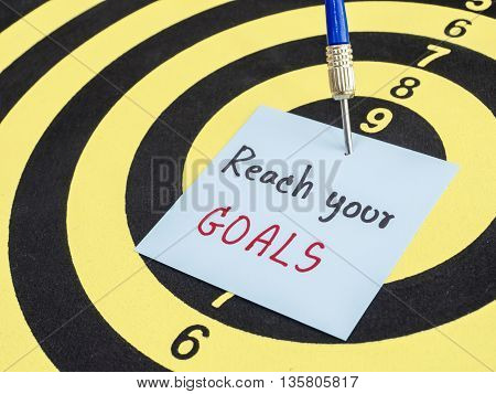 Handwriting Reach your goal on notepaper with dart arrow and dart board. (Business concept)
