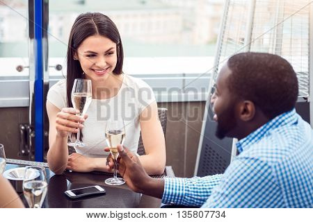 Full of joy. Cheerful delighted smiling friends sitting in the cafe and drinking champagne while celebrating