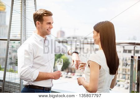 Great view. Pleasant delighted young couple drinking champagne and standing on the balcony while resting together