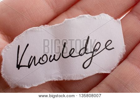 Knowledge written torn paper on a white background