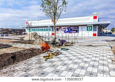 Zrenjanin Vojvodina Serbia - 09. October 2015: Garden workers are planting a tree at new shopping mall