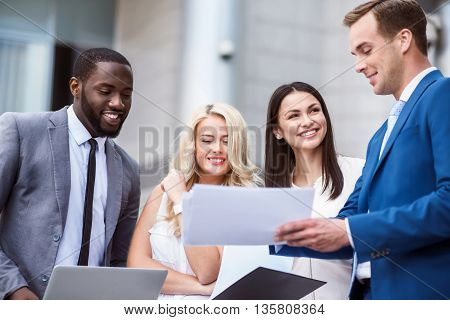 Work together. Cheerful smiling delighted colleagues working with papers and discussing project while standing near office building