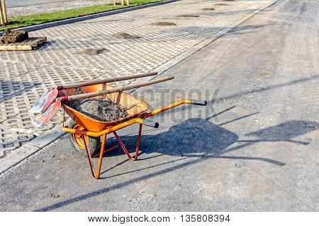 Wheelbarrow with tools for cleaning at parking lot.