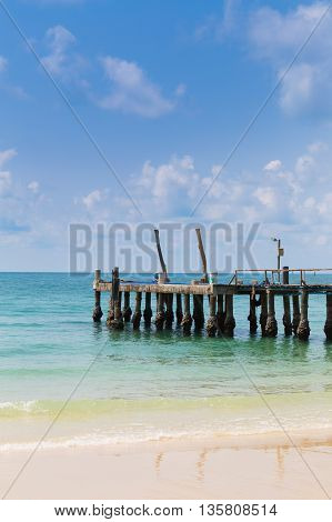 Fishing pier or wooden bridge on the beach leading to the sea, natural landscape background