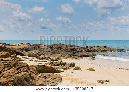 Rocky and sand beach over seacoast skyline, natural landscape background