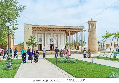 BUKHARA UZBEKISTAN - APRIL 29 2015: The frontage of Khakim Kushbegi Mosque with the numerous pilgrims around it on April 29 in Bukhara.