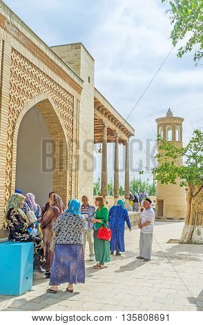 BUKHARA UZBEKISTAN - APRIL 29 2015: The line of the worshipers next to the entrance to Khakim Kushbegi Mosque on April 29 in Bukhara.
