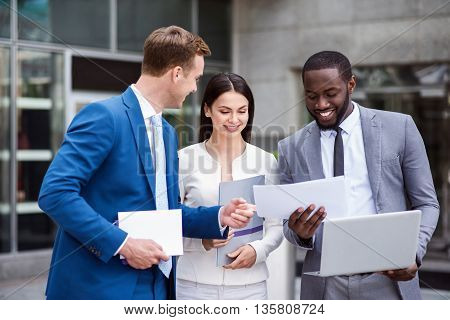 Have a look. Pleasant cheerful delighted colleagues working with papers and talking while standing near office building