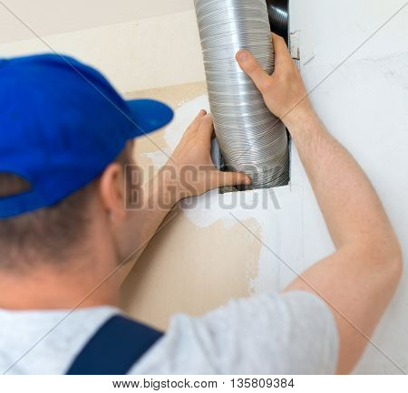 Man setting up the ventilation system indoors.