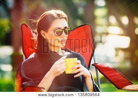 Portrait of beautiful calm woman sitting outdoors and with pleasure drinking tea, enjoying bright sunny spring day, spending weekend in countryside