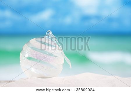 christmas glass ball on white sand beach with seascape background