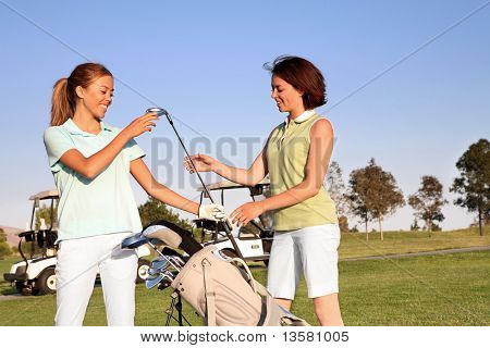Two pretty women golfers selecting a golf club