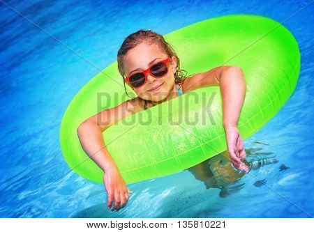 Cute little girl swimming in the pool in big bright green rubber ring, having fun in aquapark, happy summer holidays on the beach