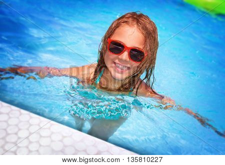 Portrait of cute happy little girl having fun in swimming pool, adorable baby spending summer vacation on the beach resort