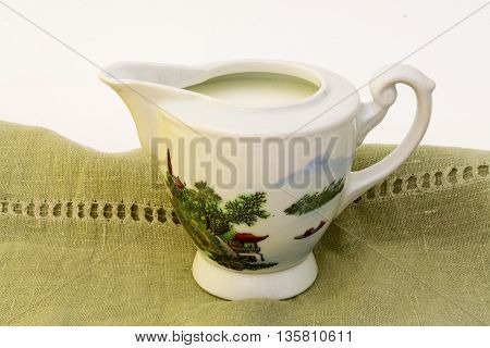 Antique milk jug with a Japanese painting on green linen tablecloth.