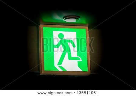 Emergency exit symbol glowing green in the blacked out background