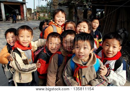 Li'an Village China - November 26 2007: A group of smiling Chinese children wearing their red school scarves gather outside their school