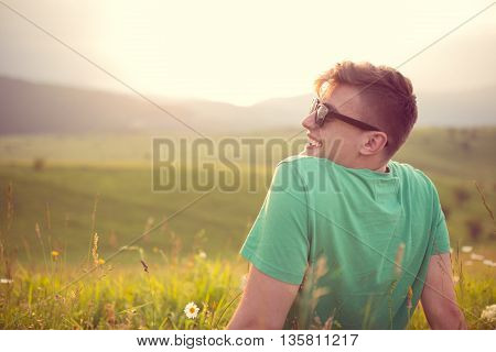Carefree happy man sitting on green grass meadow in mountains enjoying the sun on his face.Enjoying nature sunset.Freedom.Enjoyment.Relaxing in mountains at sunrise.Sunshine.Daydreaming