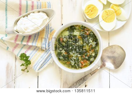 Nettle soup served with egg and sour cream, top view