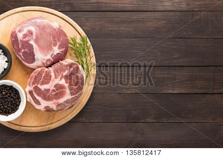 Top View Raw Pork Chop Steak And Garlic, Pepper On Wooden Background. Copy Space For Text