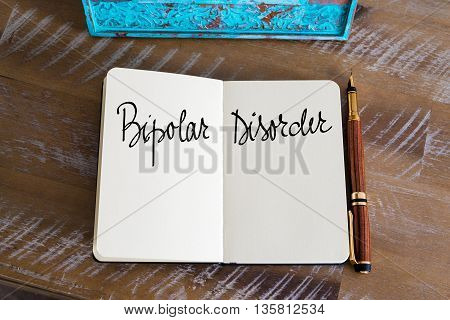 Bipolar Disorder handwritten over notebook, copy space available