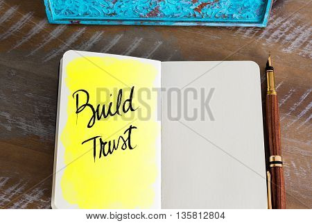 Text Build Trust over notebook, copy space available