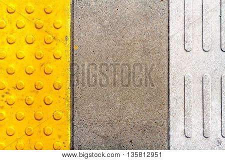 Yellow and white warning tiles on railway station