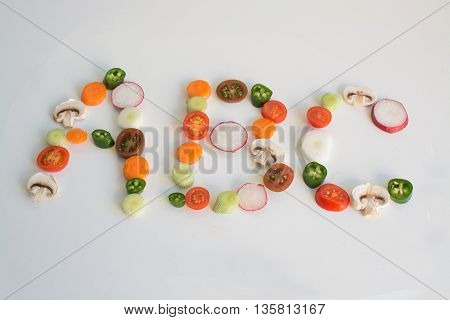 ABC spelled out from vegetable slices on a white background