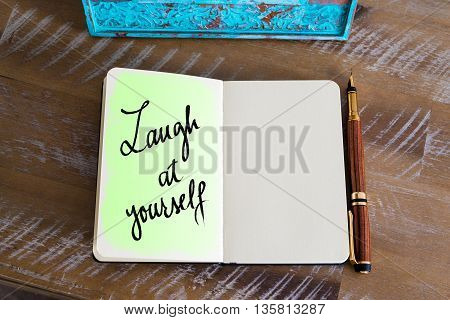 Text Laugh At Yourself handwritten over notebook, copy space available