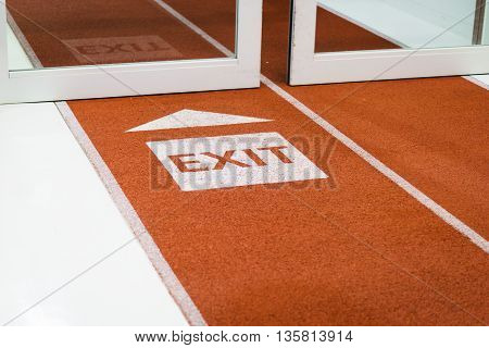 White exit sign arrow painted on the carpet - airport / transportation sign