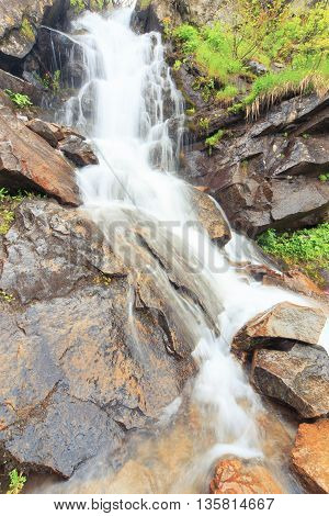 Beautiful cascading full-flowing waterfall in the mountains.