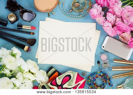 styled feminine desktop - woman fashion flat lay items on blue wooden background, copy space on aged photo paper
