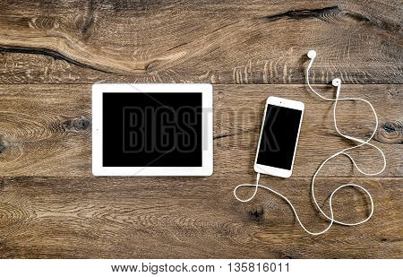 Phone with headphones and tablet pc on wooden background. Mockup screen electronic devices. Flat lay